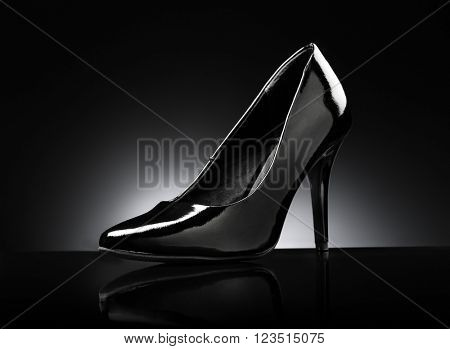 Black glossy ladies stiletto heel pump on black reflective background.