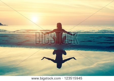 Female silhouette doing exercise at beautiful sunset on the sea beach. Yoga, fitness and healthy lifestyle.
