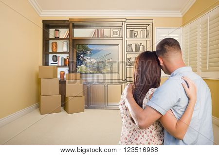 Young Military Couple Looking At Drawing of Entertainment Unit In Room With Moving Boxes.