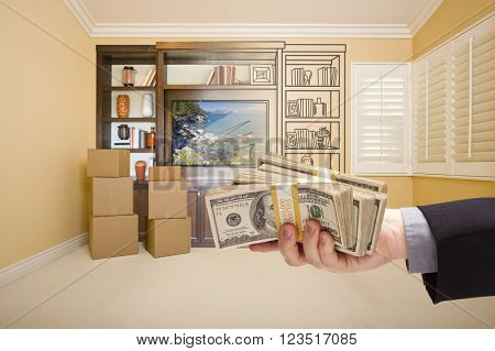 Hand Holding Out Cash Over Drawing of Entertainment Unit In Room With Moving Boxes.