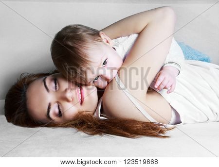 young beautiful mother and her one year old baby at home