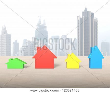 Four colorful houses on wooden table, with city skyscraper background.