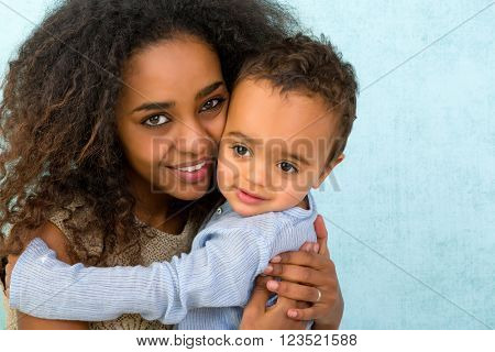 Little 18 month old African boy hugging his mother