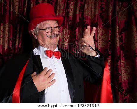 Senior illusionist on stage bending a spoon
