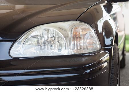 Closeup headlight of black coupe, stock photo