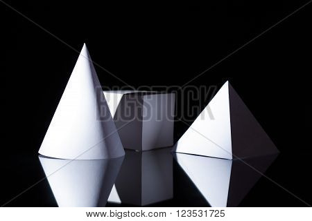 Geometry concept. Set of various paper shapes on dark background ** Note: Visible grain at 100%, best at smaller sizes