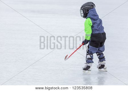 Little boy skating and playing hockey at outdoor ice rink