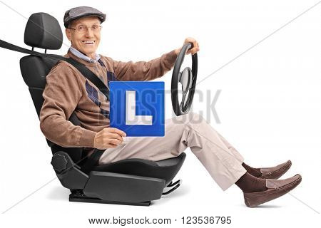 Cheerful senior holding an L-sign and holding a steering wheel seated on a car seat isolated on white background