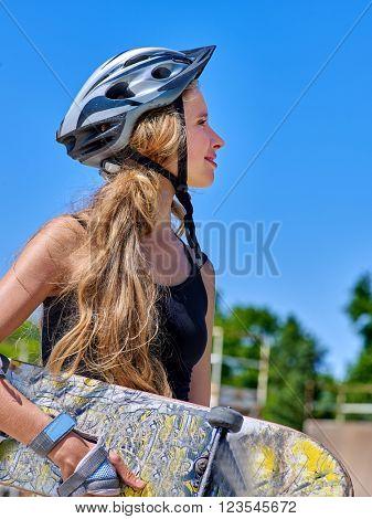 Teen in profile skateboarding keeps her skateboard . Skateboard girl style.