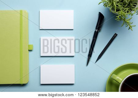 Business card blank, notepad, flower, coffee cup and pen at office desk table top view. Corporate stationery branding mock-up.