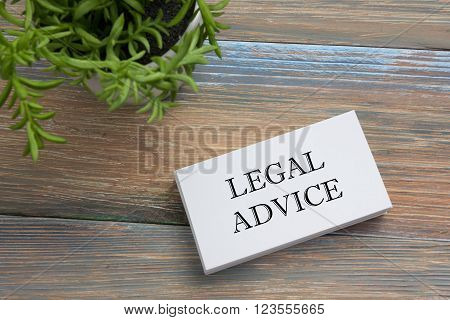 Legal Advice. Business card with message and flower. Office supplies on desk table top view.
