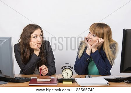 Two Girls In The Office Waiting For The End Of Working Hours On The Clock And Looking At Each Other