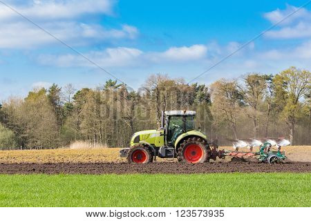 Peasant on tractor plowing sandy soil in spring season