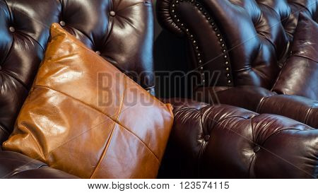 Leather sofa and pillows in retro tone with selective focus on the pillows