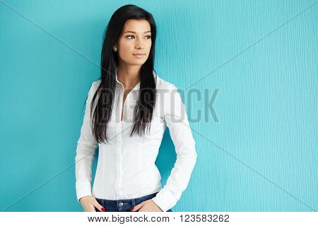 Young Beautiful Woman Leaning Against A Blue Wall