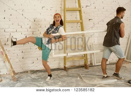 Happy young couple having fun at home renovation, holding window frame.