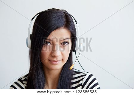 Portrait Of Support Female Phone Operator With Headset, Looking Up