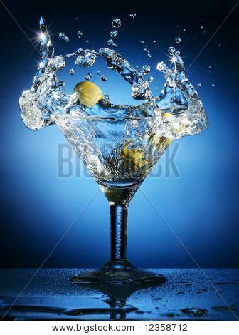 Olive falls in a glass of martini. Thus there is a splash.