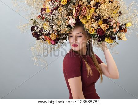 Beauty fashion female portrait with large garland dried flowers. Beautiful woman with wreath of roses
