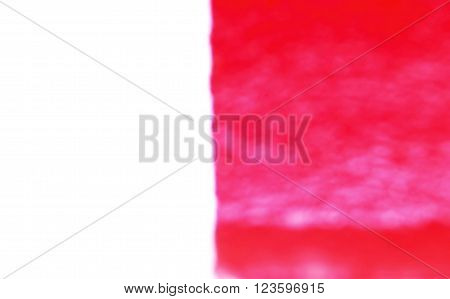 Blurred image of red-white kerb line or curb stone border on the asphalt road with wet paint. Footpath background.