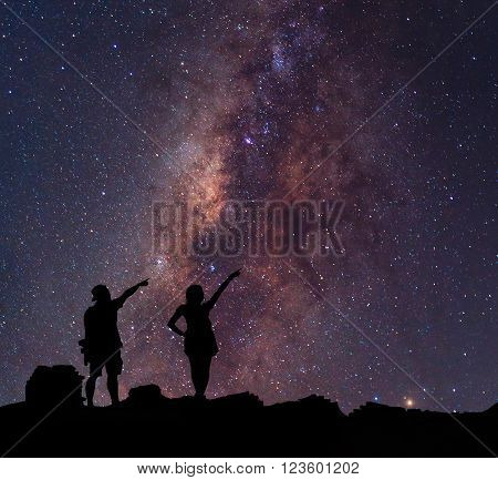 Star-catcher. A person is standing next to the Milky Way galaxy