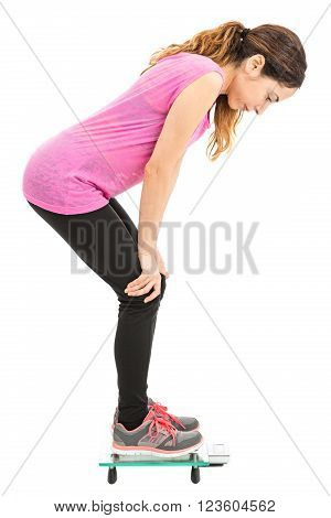 Caucasian woman on diet checking her weight loss on scale. Isolated on white background.