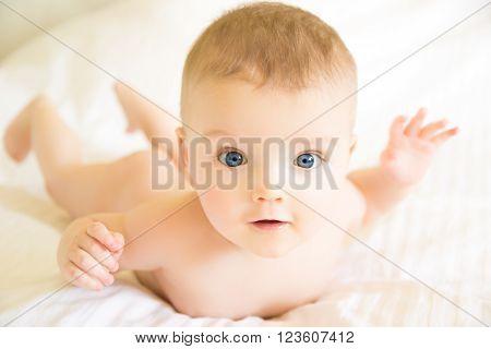 Little nude baby lying on a blanket