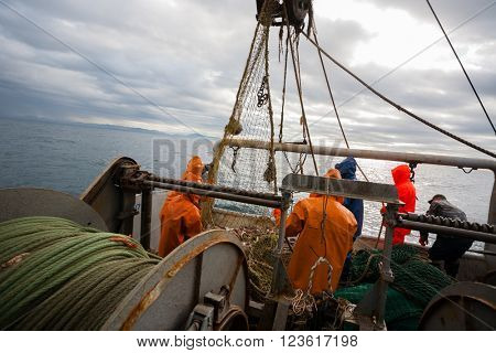 Fishermen in waterproof suits on the deck of the fishing seiner. Morning time.