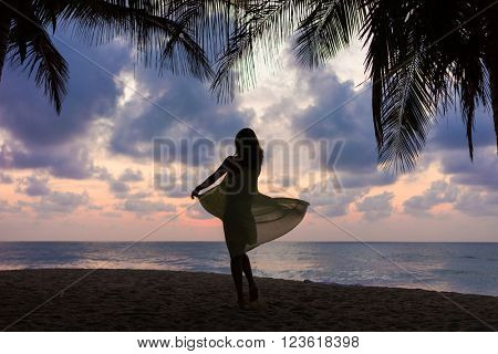 Woman on the tropical beach at sunset dancing  under the coconut trees