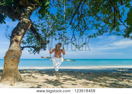 Woman on a swing at the tropical beach in Thailand