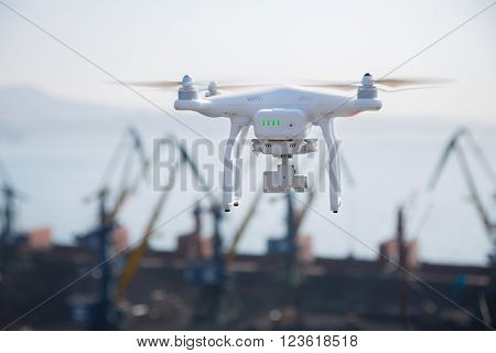 Flying drone armed with camera on a sky background