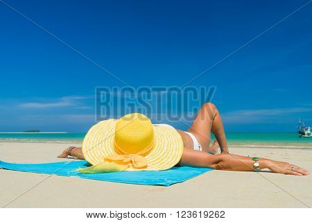 Girl on a tropical beach with a yellow hat