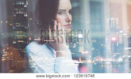 Photo business woman wearing white shirt, talking smartphone. Open space loft office. Panoramic windows, night city background.