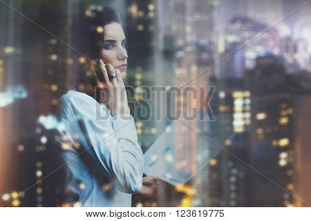 Photo woman wearing white shirt, talking smartphone and holding business documents in hands. Open space loft office. Panoramic windows, night city background. Horizontal mockup, bokeh.