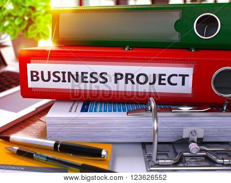 Red Ring Binder with Inscription Business Project on Background of Working Table with Office Supplies and Laptop. Business Project Business Concept on Blurred Background. 3D Render.