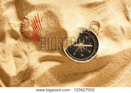 Black Compass And Sea Shell In Sand