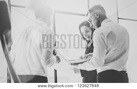 Business team work process. Photo professional crew working with new startup project. Project managers meeting. Analyze business plans laptop. Blurred background, film effect, black white.