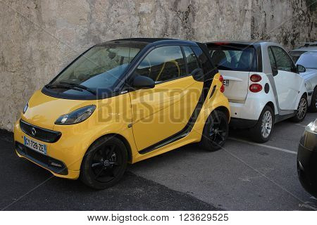 Saint-Paul-de-Vence France - March 22 2016: Yellow Smart Fortwo Cityflame and White Smart Fortwo Parked in the Street of Saint-Paul-de-Vence France
