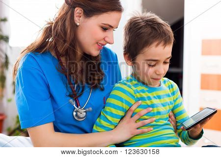 Young pediatrician doctor playing with a little boy to become friends.