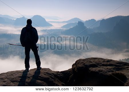 Misty Day In Rocky Mountains. Silhouette Of Tourist With Poles In Hand. Hiker Stand On Rocky View Po