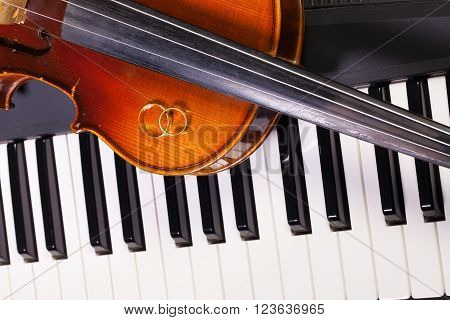 Detail of piano keyboard old violin and wedding rings