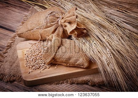 Fresh bread, baked goods, harvest on the farm, delicious food, wheat ears, cutting board, a burlap sack of grain, healthy food, a table of old wood, close-up corn, wheat grain spillage