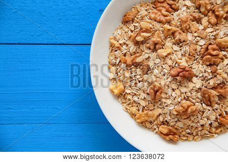 Dry Oatmeal Flakes  With Walnuts In A White Plate On A Blue Wooden Table, The Decor Of The Napkin. T