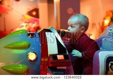 Baby playing arcade game machine at an amusement park ** Note: Visible grain at 100%, best at smaller sizes