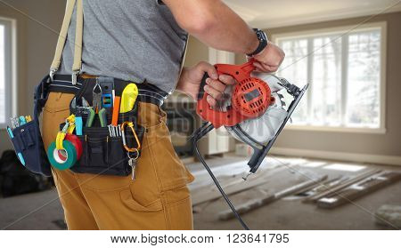 Hands of construction builder with electric saw.
