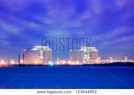 Industrial lliquefied natural gas (LNG) reservoir tanks in sea port in twilight