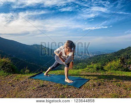 Sporty fit woman practices Ashtanga Vinyasa yoga asana Utthita Parsvakonasana varitation -  extended side angle pose outdoors in mountains in the  morning