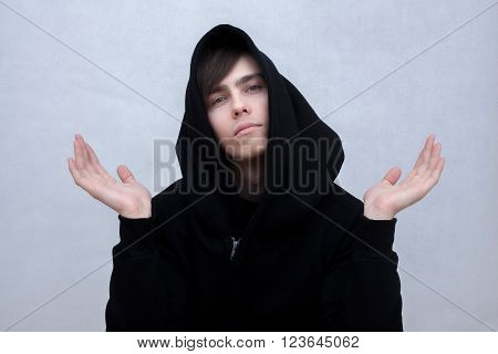 a white young man in a black hood throws up his hands