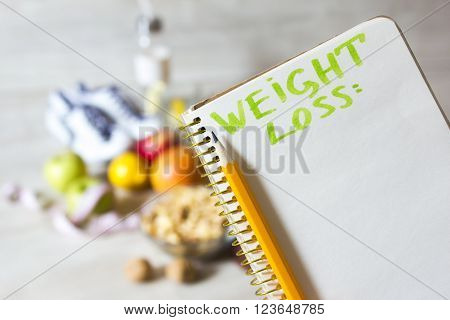 paper notebook for weight loss plan and pencil and healthy diet food & sport  sneakers in the background