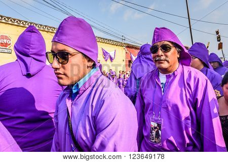 Antigua Guatemala - March 24 2016: Locals dressed as penitents called cucuruchos in Holy Thursday procession in colonial town with most famous Holy Week celebrations in Latin America.